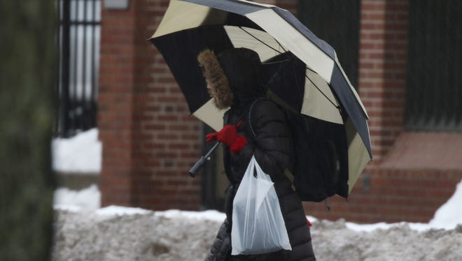 A pedestrian bundled against the cold and the steady rain Wednesday crosses State Street.