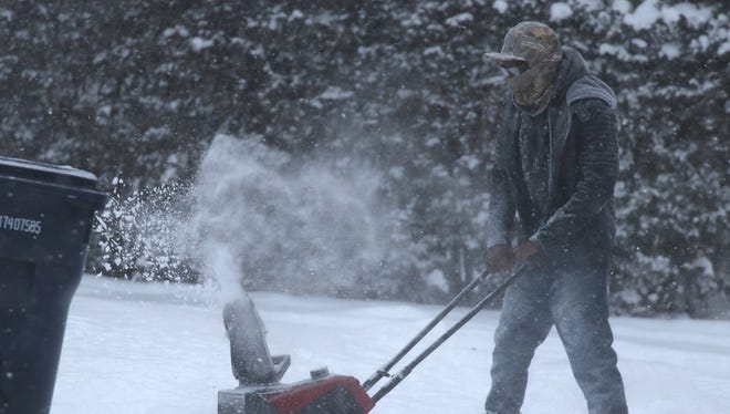 William Lundy of Irondequoit clears out his neighbor's driveway on Second Street.