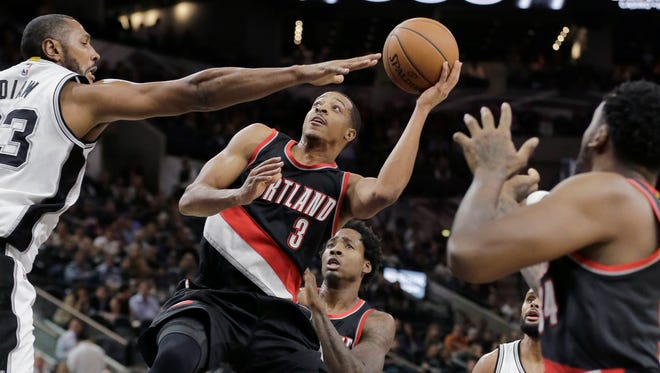 Portland Trail Blazers' C.J. McCollum (3) is defended by San Antonio Spurs' Boris Diaw (33) as he tries to score during the first half of an NBA basketball game, Monday, Nov. 16, 2015, in San Antonio.