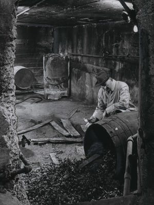 William A. Eschenburg examines an old barrel found in secret underground rooms behind an old house at 833 N. Hawley Road.  Eschenburg, who was building an apartment house at the site, said he planned to use the underground rooms as a fall-out shelter for tenants. This photo was published in the Dec. 10, 1961, Milwaukee Journal.