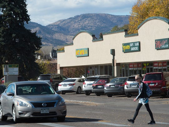 A woman walks across West Elizabeth Street in the Campus West area of Fort Collins on Tuesday.