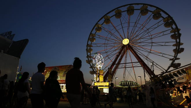 Crowds head to the midway Friday, Aug. 14, 2015, during the Iowa State Fair in Des Moines.