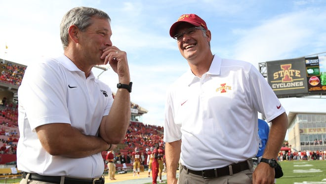 Iowa head coach Kirk Ferentz and Iowa State head coach Paul Rhoads talk before an NCAA college football game between the University of Iowa and Iowa State on Saturday, Sept. 15, 2013, at Jack Trice Stadium in Ames, Iowa.