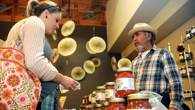Kelly Beattie, of El Paso, left, looks over the selection of salsa at Rogelio Villegas' table on Saturday during the first HomeGrown: A New Mexico Food Show & Gift Market at the New Mexico Farm & Ranch Heritage Museum last year.