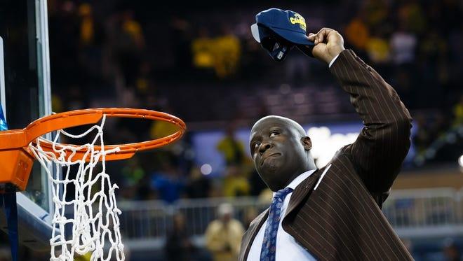 Michigan assistant basketball coach Bacari Alexander cuts down the net after winning the Big Ten championship March 8, 2014.