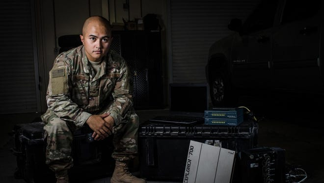 Air Force Staff Sgt. Junbryan Samson, a cyber network technician assigned to the U.S. Air Forces Central Command communications division at the Combined Air Operations Center, sits next to a communications fly-away kit July 31, 2017, at Al Udeid Air Base, Qatar.