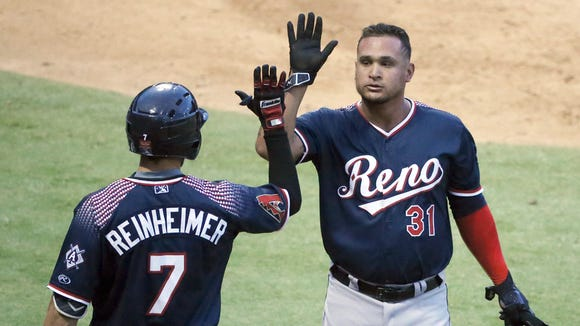 Oswaldo Arcia, 31, of the Reno Aces is congratulated by teammate Jack Reinheimer after crossing home plate for the team's 9th run of their game against the El Paso Chihuahuas Monday night at Southwest University Park.