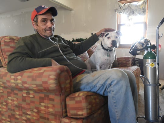 """William """"Bill"""" Murray, 61, sits on a couch inside a rural Mountain Home residence with his dog, Sassy. Murray recently moved into the unfinished home after several area churches and personal donors got together to help pay for renovation. A volunteer working on the house reported a theft on Friday after noticing several tools missing."""