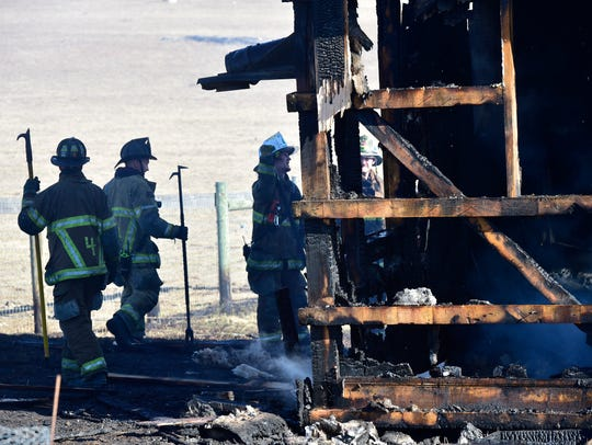 Firefighters continue to work hotspots at a greenhouse