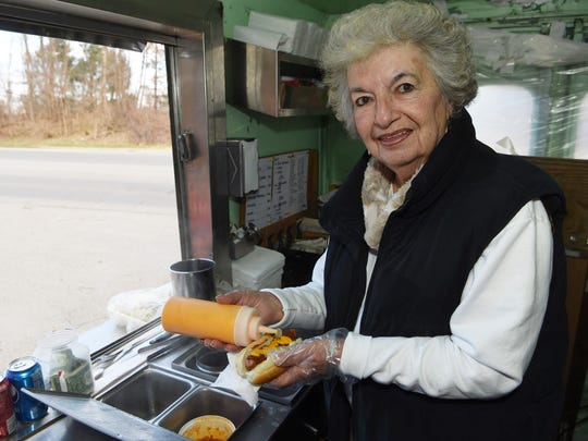 Carole Crusco, owner of Carole's Hot Dogs, stands inside of her food truck as she prepares a hot dog off of St. Andrew Road in Hyde Park.