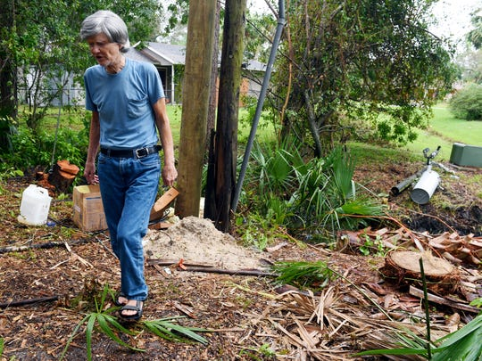 Bill Herman walks through the downed trees and equipment