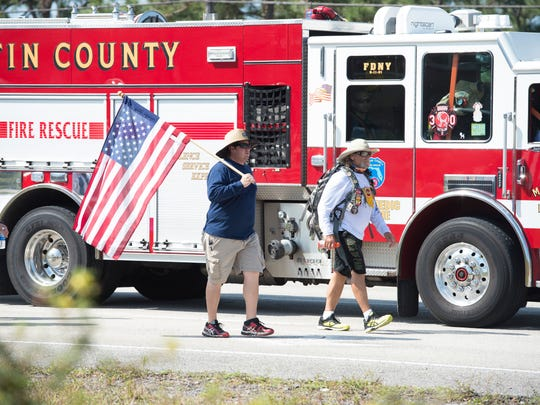 "Martin County Fire Rescue firefighter Rob Chagnon (left) and Tom ""Bull"" Hill lead the March of the Bull awareness walk for firefighters on Monday, April 9, 2018 as a crew escorted by Martin County Fire Rescue Station 30 walked north on U.S. 1 between Cove Road and Indian Street in Stuart."