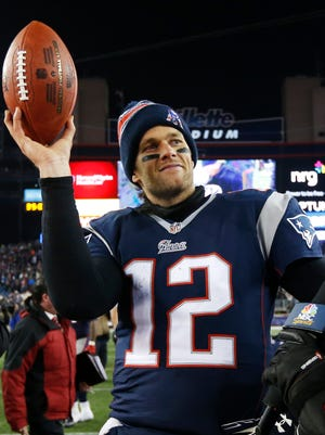 New England Patriots quarterback Tom Brady holds up the game ball after an NFL divisional playoff football game against the Baltimore Ravens.