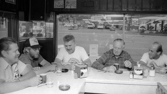 """Patrons enjoy conversation and coffee at Dick's Cafe on St. George Boulevard in the then image taken by Spectrum photographer Nancy Rhodes in May of 1992. According to the Washington County Historical Society, E. N. """"Dick"""" Hammer opened an 8-stool hamburger stand on St. George Boulevard in 1935. He later used the profits from that stand to build Dick's Cafe with a horseshoe counter and two dining rooms. The cafe was demolished around the turn of the century and a two-story building to house Sun First Bank was constructed on the site. Though the window behind the Dick's Cafe patrons, the old Handy Mart that was across the street and the Best Western Coral Hills Motel can be seen. The motel is still there and so is the Handy Mart as can be seen in the now image taken by Spectrum photographer Jud Burkett. The Handy Mart has since been re-purposed and now is the home of Studio 359 Salon and Day Spa."""