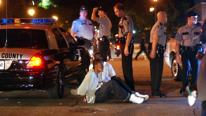 Handcuffed suspects sit on the road as Augusta-Richmond County Sheriff's Deputies wait to transport them to jail during First Friday on Broad Street Friday evening.