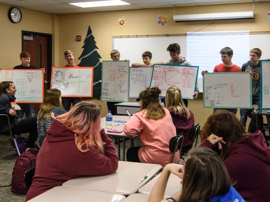 Students in math teacher Kendra Barrett's geometry class hold up whiteboards detailing work done in small groups to solve a problem projected on the whiteboard.