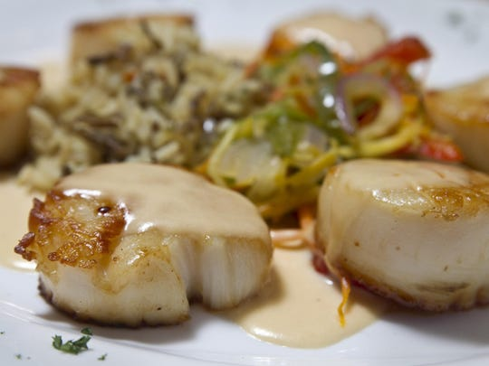 Seared diver scallops, served with a mango coconut rum sauce, at Runners Seafood Restaurant and Market.