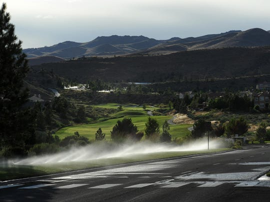 Sprinklers are seen in use on common roadside areas at the Somersett development in northwest Reno at approximately 6:30 pm on July 9, 2015.