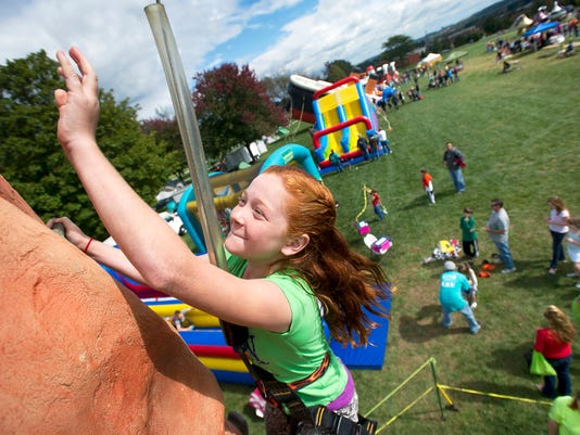 11-year-old Lindsey Ulerick of Springettsbury Township makes it to the top of the climbing wall at the Saturday in the Park event at Springettsbury Park