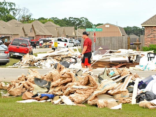 A Ragin' Cajuns football player walks past piles of debris while helping with flooded homes in Youngsville after the recent flooding.