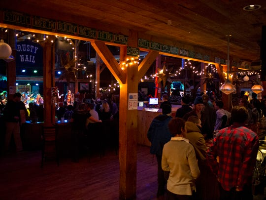 Gang of Thieves performing on stage at the Rusty Nail in Stowe, Friday, January 9th, 2015. The Venue features a large dance floor, colorful lighting and a post and beam barn aesthetic.