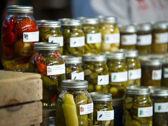 Farmer Sue's pickle jars glint in the morning sunlight at the winter farmers market hosted at the Memorial Auditorium in Burlington.