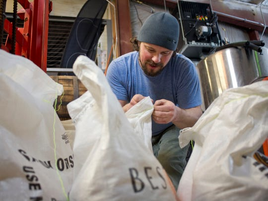 Brian Eckert owner and head brewer of Four Quarters Brewing in Winooski, gathers all the ingredients he will need to begin work on Funky Monkey, a collaboration brew that with The Monkey House, a Winooski bar. Eckert is collaborating with local businesses to create special beers for his brewery's one-year anniversary.