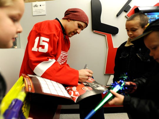 Riley Sheahan signs a calendar with his photo on it for hospital patient Michael Williamson, 6, of Lincoln Park.