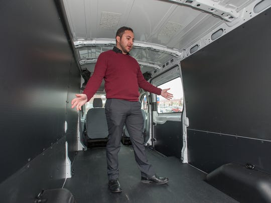 Joe Celentino, sales representative at Village Ford in Dearborn, shows how the roominess inside a Transit van. Ford Motor Co. says sales of the new Transit, which replaced the E-Series, have been brisk, with nearly 5,000 sold in November alone.