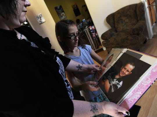 Cee Cee Ott, a 9-year-old transgender girl, looks at photos of herself as a young boy with her mother Shanna Ott at their home in Reno.