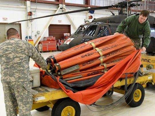 Chief Warrant Officer 3 B.J. Koons, left, and Staff Sgt. Doug Edmisten uncover one of the two Bambi Buckets assigned to the unit in Alcoa Tuesday, Jan. 17, 2017.