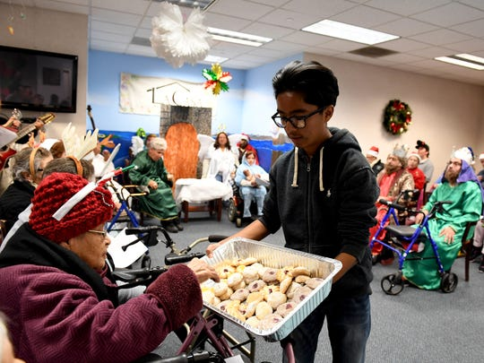 Volunteer Daniel Ruiz serves cookies to participants at the La Casa Adult Day Health Center during it's annual Christmas Eve Posada.