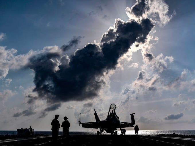 Sailors on the carrier USS Harry S. Truman work near