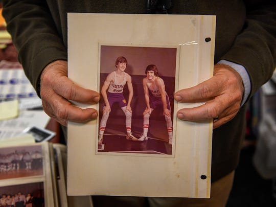 Coach Frank Simpson holds a scrapbook photo from when he and his brother Patrick wrestled side by side as youths in Nashville.