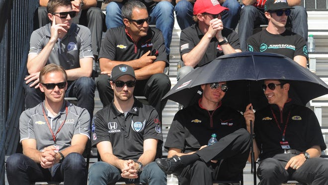 Will Power and Helio Castroneves  use an umbrella during the drivers meeting Saturday May 24,  2014 at The Indianapolis Motor Speedway