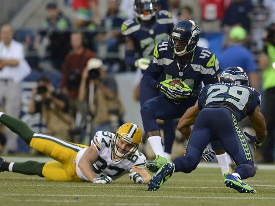 Seattle Seahawks cornerback Byron Maxwell (41) makes an interception past Green Bay Packers receiver Jordy Nelson in the third quarter during their Week 1 game at CenturyLink Field in Seattle.