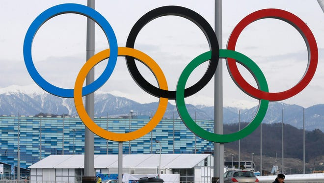 A Russian police officer walks by the Olympic rings in front of the Iceberg Skating Palace at the Olympic Park in the Adler district of Sochi Jan. 26.