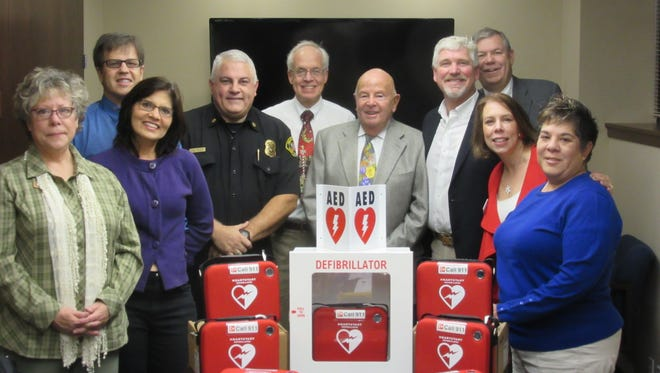 The Salem Fire Foundation Board celebrates getting AED's for police cars.
