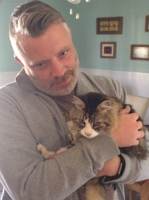 San Angelo residents Randall Case and Cutty the Cat pose for a photo on Saturday, Dec. 9, after their reunion on Friday. Cutty was missing for almost 3 weeks.