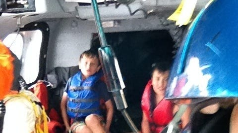 Thomas Alter and Zachary Suri sit on board a Coast Guard Dolphin helicopter from Air Station Traverse City, Mich., after being rescued July 11, 2014. The boys, along with Suri's mother, were rescued from Whaleback Shoal in Green Bay after being stranded on the water overnight when their kayaks went adrift.