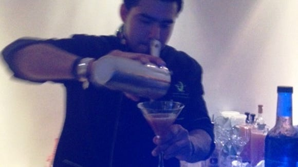 A bartender at Junior Merino's Liquid Chef stand mixes up a Dragonfly cocktail at the Chefs' Night Out party in New York.