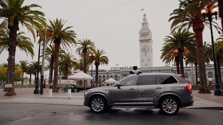 A gray Volvo XC90 SUV with Uber logos and visible self-driving hardware parked on a city street in San Francisco.
