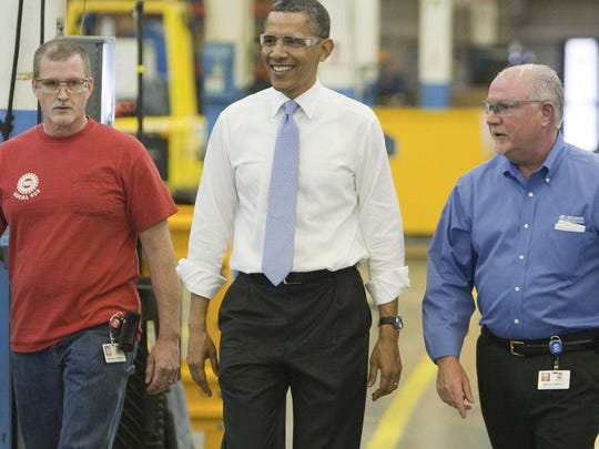 President Barack Obama walked with Richard Thomas (left) and Mike Clements as they tour the Allison Transmission company on a visit to the manufacturer on May 6, 2011. Obama was there to promote a $62.8 million federal grant to help the Indianapolis company develop hybrid transmissions.