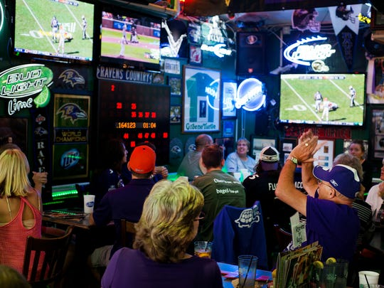 Baltimore Raven fans react to their defense sacking the Cleavland Browns quarterback while they watch the game at the Greene Turtle in North Ocean City.