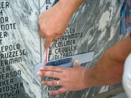 Scott Dunn takes a rubbing of his father's name on the veterans wall at Coral Ridge Cemetery on Monday, May 29, 2017, following the Memorial Day Ceremony.