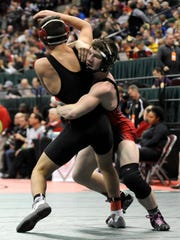 Ridgedale's Kalib Patterson and Pleasant's Carter Wolf wrestle Saturday during the State Wrestling Championships at the Jerome Schottenstein Center in Columbus. Wolf won the Division III 120-pound match 4-3 to take seventh place.