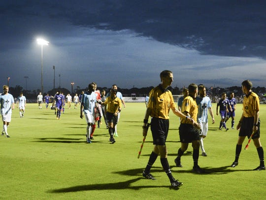 OCB players and officials leave the field due to a lightning delay during their season opening game Saturday evening.