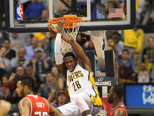 Indiana's Ian Mahinmi hangs onto the basket after slamming home a shot and getting fouled in the fourth quarter as the Indiana Pacers beat the Atlanta Hawks 108-98 at Bankers Life Fieldhouse Tuesday February 18, 2014.