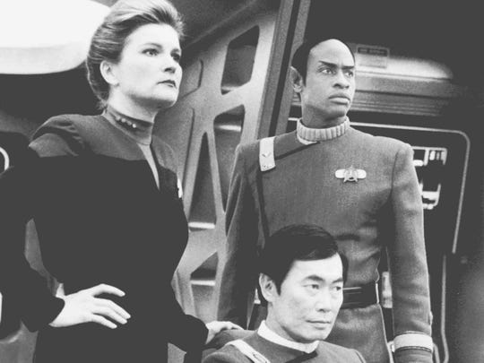 """When Captain Kathryn Janeway (Kate Mulgrew) mind-melds with Tuvok (Tim Russ), they are taken back to the Bridge of the U.S.S. Excelsior with Captain Hikaru Sulu (George Takei, center) in command, on """"Star Trek: Voyager."""" This episode commemorated the 30th anniversary of """"Star Trek."""""""