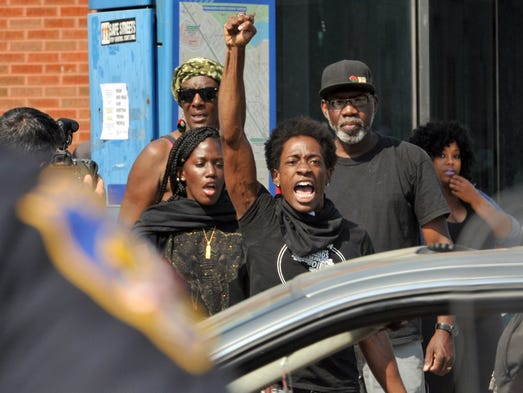 Protesters chant in front of police in Baltimore. Lt.